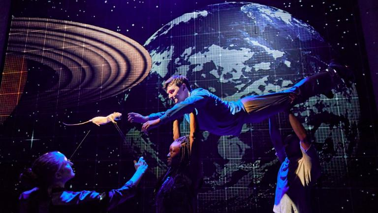 The Curioius Incident of the Dog in the Night-Time - Christopher is held aloft by cast members, lying flat and reaching out for a white rat, with globes projected on the background