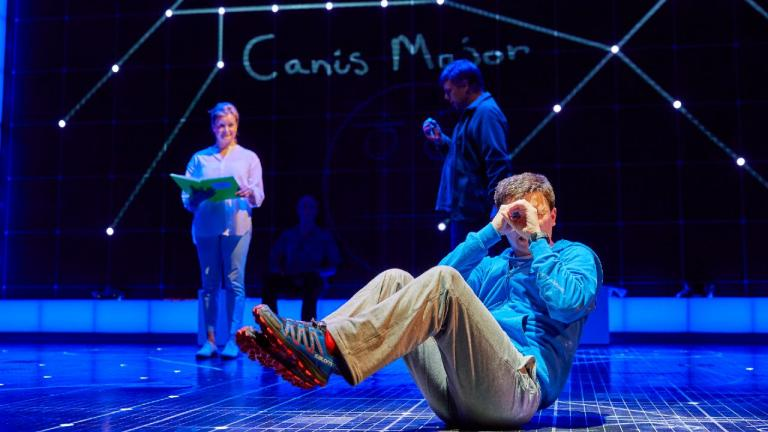 The Curioius Incident of the Dog in the Night-Time - Christopher sits on teh floor, looking through his hands, as if through a telescope, other cast members behind him, with constellations projected behind