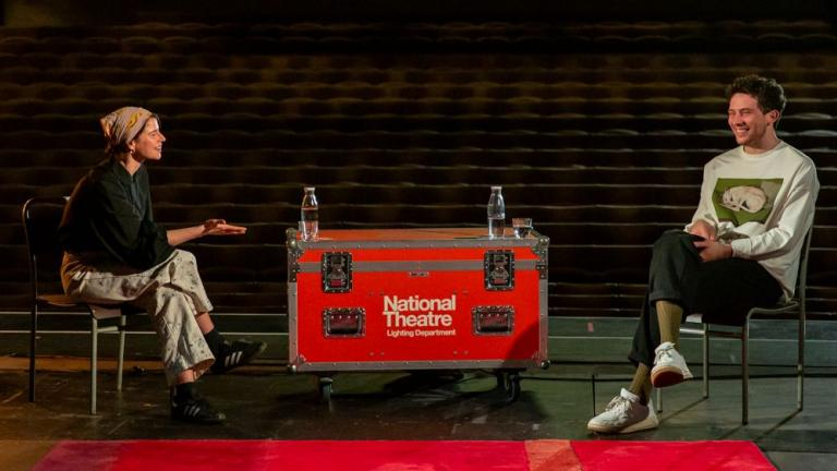 Life in Stages: photo of Jessie Buckley and Josh O'Connor sitting on bentwood chairs, with a NT Lighting Department flight case acting as a table between them, facing each other, on the Lyttelton Stage with the auditorium behind them