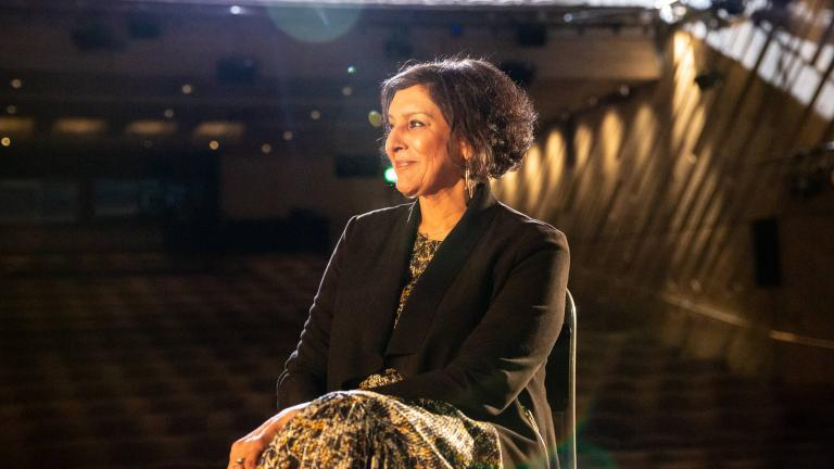 Life in Stages: photo of Meera Syal sitting on a bentwood chair, on the Lyttelton Stage with the auditorium in the background