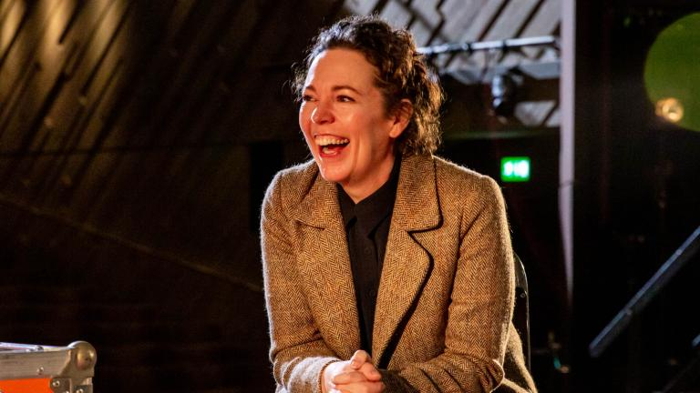 Life in Stages: photo of Olivia Coleman sitting on a bentwood chair, on the Lyttelton Stage with the auditorium in the background