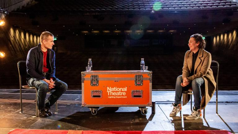 Life in Stages: photo of Olivia Colman and Rufus Norris sitting on bentwood chairs, facing each other with a NT Lighting Department flight case acting as a table between them, on the Lyttelton Stage with the auditorium behind them