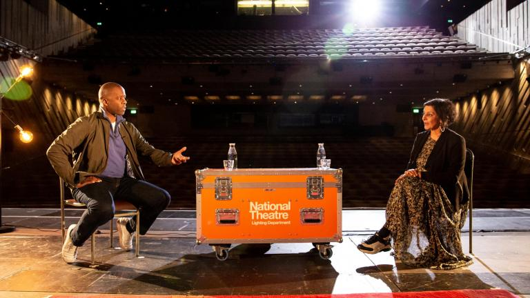 Life in Stages: photo of Adrian Lester and Meera Syal sitting on bentwood chairs, with a NT Lighting Department flight case acting as a table between them, facing each other, on the Lyttelton Stage with the auditorium behind them
