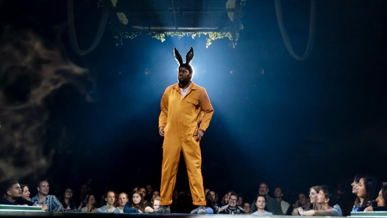 A Midsummer Nights Dream with Hamed Animashaun as Bottom, in an orange boiler suit and rabbit ears, standing on a raised stage surrounded by audience members