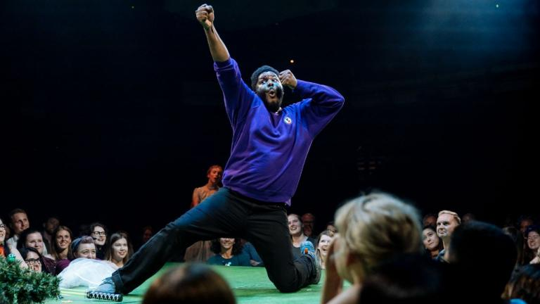 A Midsummer Nights Dream with Hamed Animashaun in a blue tracksuit top and jeans, miming drawing a bow and arrow