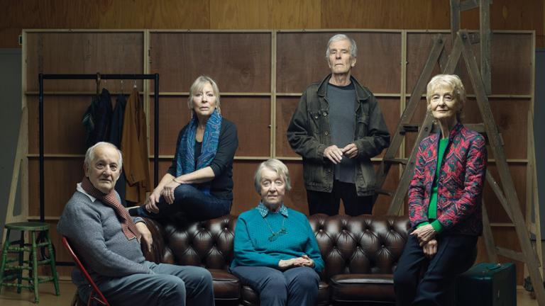 An image of five actors from Lost Without Words seated on and around a leather sofa