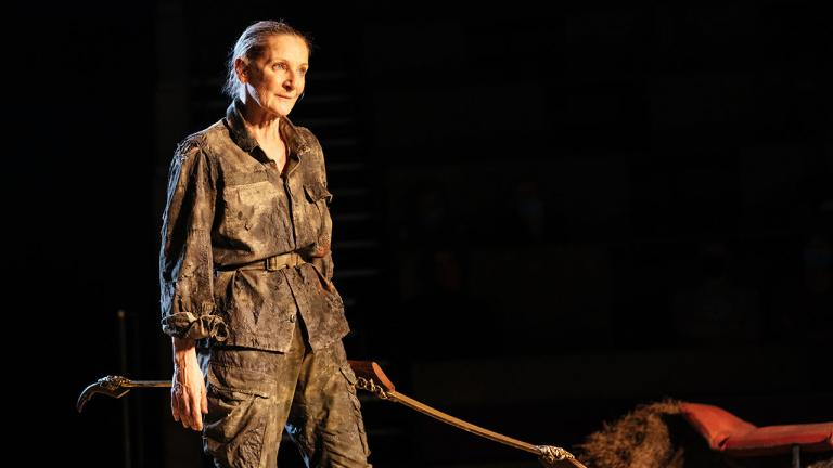 A white woman, Lesley Sharp, holding a bow wearing army uniform in Paradise at the National Theatre