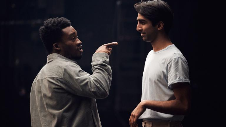 Romeo and Juliet production image with Fisayo Akinade pointing his finger at Shubham Saraf to emphasise a conversational point