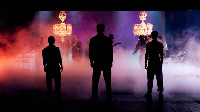 Romeo and Juliet production image with three members of the company standing in silhoutte, two large lit chandeliers beyond them