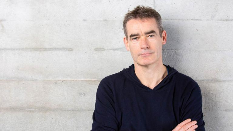 Rufus Norris stands against a plain wall.