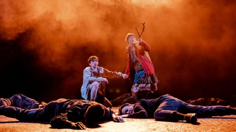 Alex and Lettie stand in the middle of bodies which lie on the ground. Alex is crouched down and Lettie is stood up – she holds a stick in her hand which she points upwards. Orange mist surrounds them.