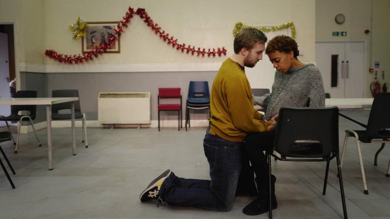 A scene from LOVE - 2 characters, a man kneeling next to a seated, pregnant woman