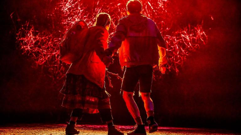 The Ocean at the End of the Lane Production Photo: Samuel Blenkin and Marli Siu walking away from the audience, towards an orange and smoke filled scene