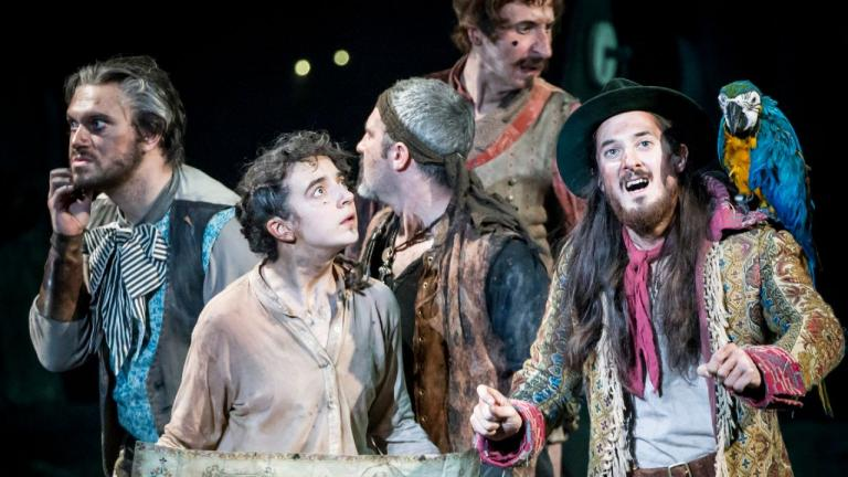 Treasure Island production image - Long John Silver, his parrot and crew and Jim (holding a map) are looking round for their bearings