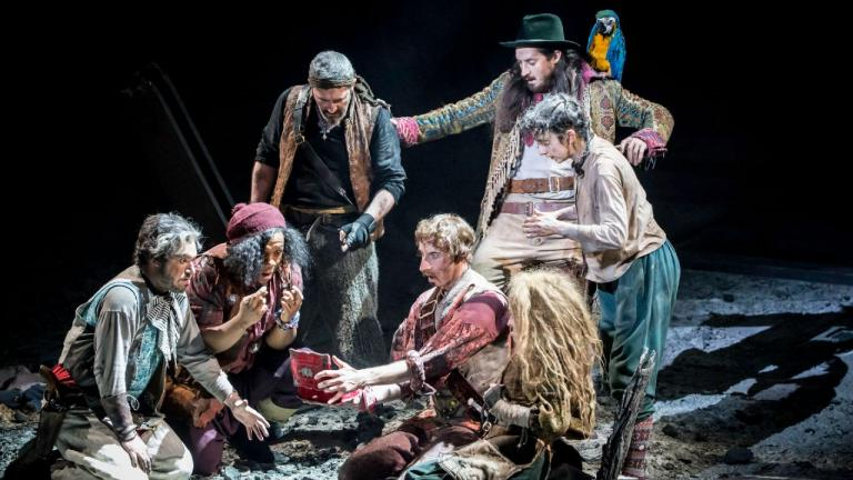 Treasure Island production image - Long John Silver, his crew, Jim and Ben Gunn gather round a small casket