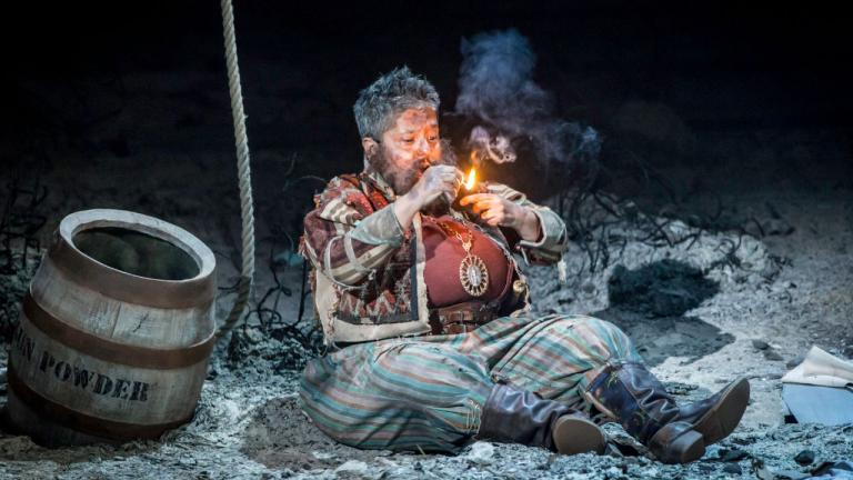 Treasure Island production image - Israel Hands sitting smoking a pipe next to a barrel of gunpowder