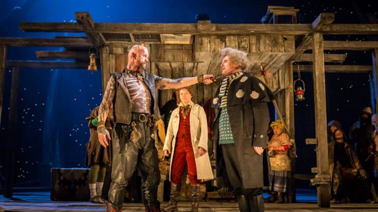 Treasure Island production image - a pirate holds his knife to the throat of a man, watched by onlookers