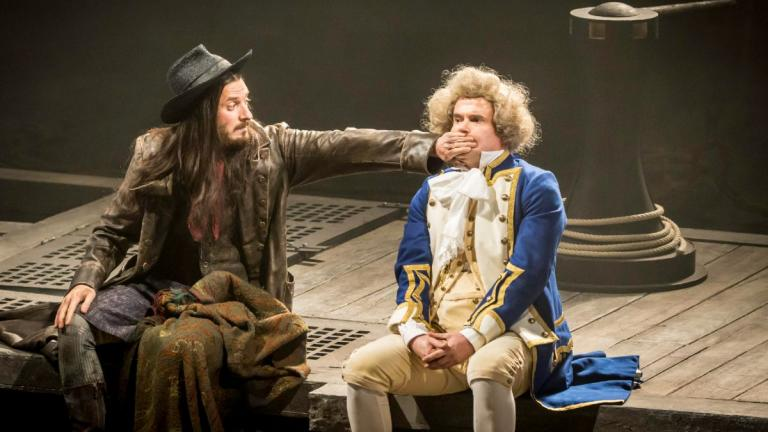 Treasure Island production image - Long John Silver holds his hand across Captain Smollet's mouth, as they sit together on a quay side