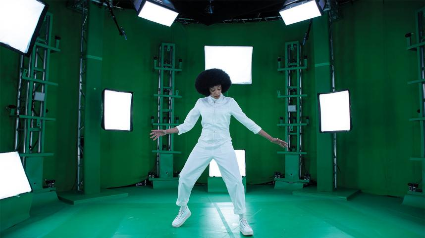 All Kinds Of Limbo photo of Nubiya Brandon in a white jump-suit in a green room