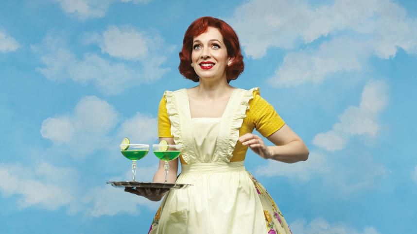 Home I'm Darling. Photograph of Katherine Parkinson, wearing a 1950s floral skirt and an apron, holding a tray with two cocktails