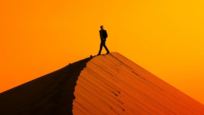Peter Gynt - image of a lone figure walking along the ridge of a desert dune