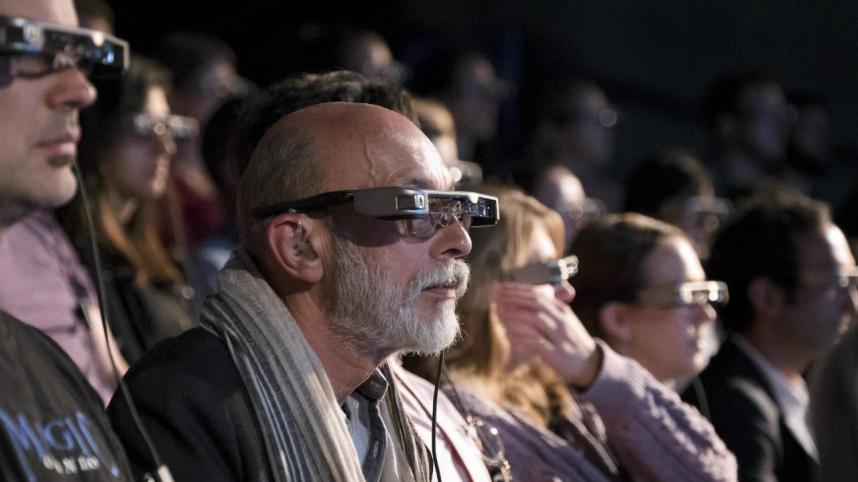 People wearing Smart Caption Glasses at a performance in the theatre