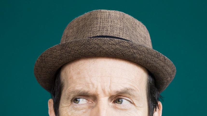 Tartuffe poster with Denis O'Hare, wearing a trilby hat