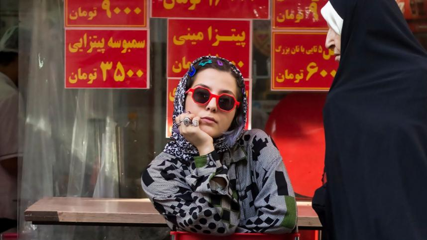 Welcome to Iran. Poster image with photo of a seated young Iranian woman, in trousers, patterned top and headscarf, and red-rimmed sunglasses, and an older woman walking by, dressed all in black, except for a white strip along the front of her headscarf.