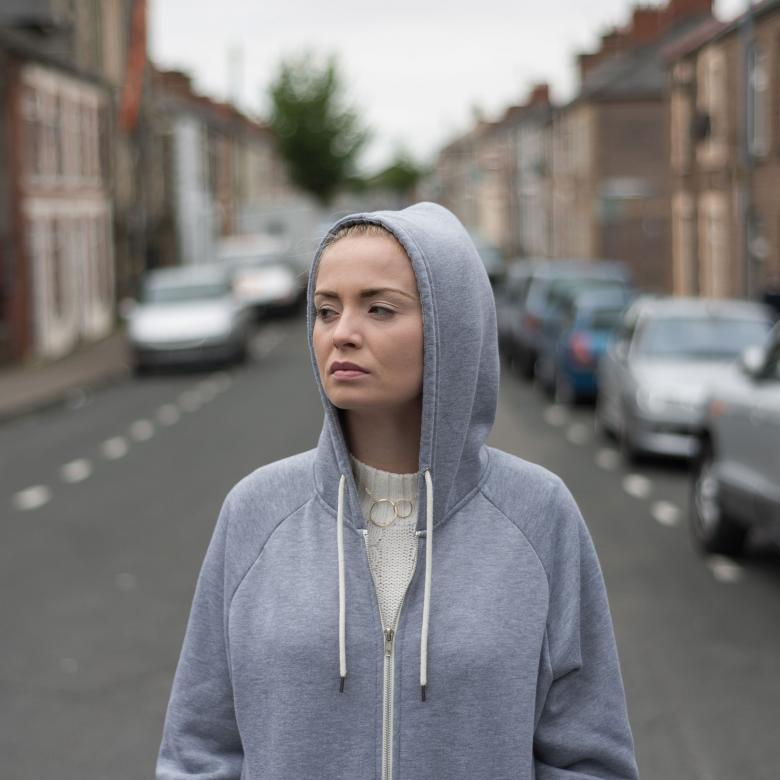Iphigenia in Splott poster. Photo of a young woman in a grey hoodie