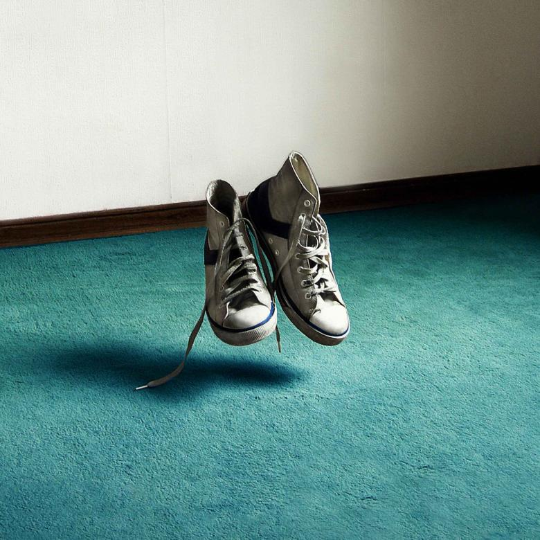 After Life - poster image of a pair of old, white canvas basketball high-top trainers, floating above a teal coloured carpet, in an otherwise bare room with white walls