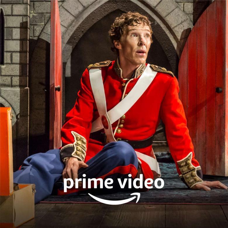 Amazon Prime - Benedict Cumberbatch as Hamlet, in a dress uniform with red jacket and blue trousers, seated.