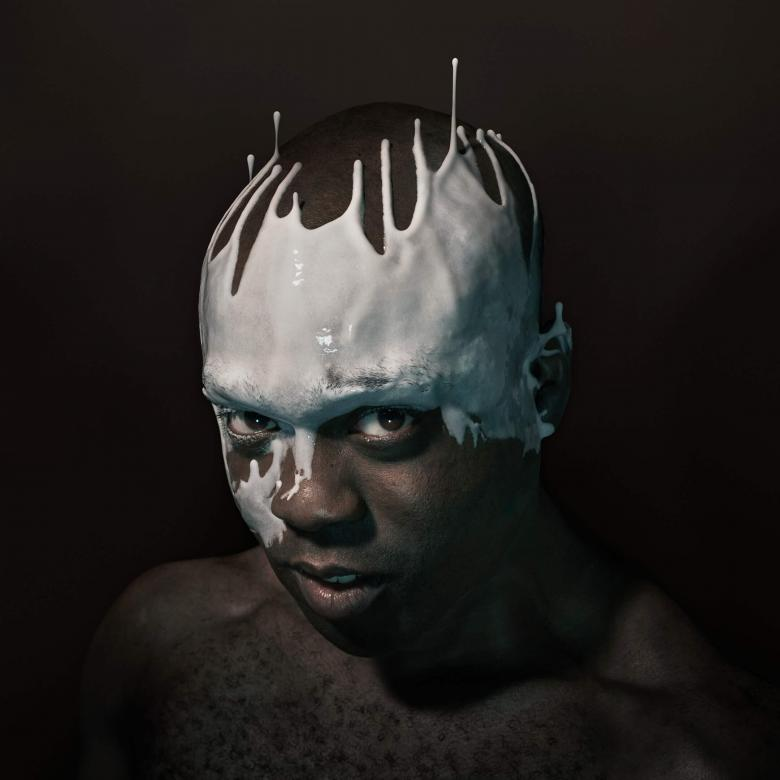 An Octoroon poster with Ken Mwosu, bare-chested with head splattered with white liquid, seemingly dripping upwards