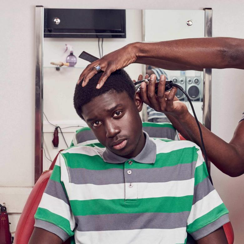 Barber Shop Chronicles - photo of a young man having hair clipped
