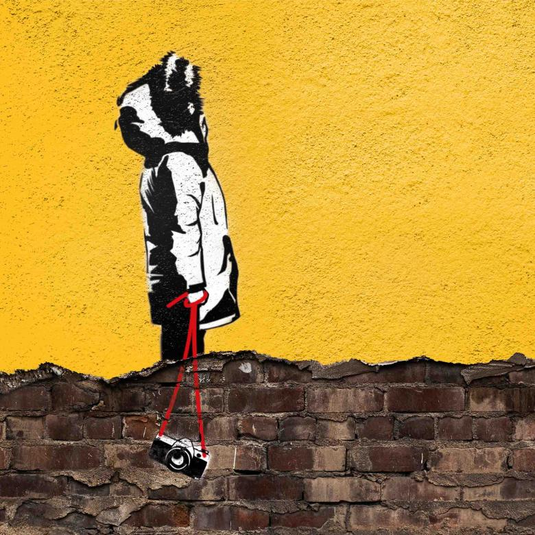 East is East poster, with a graffiti image of a figure in profile, wearing a parka coat, hood-up, carrying a camera on a strap, against a rendered wall in yellow with the title of the play spray-painted in white