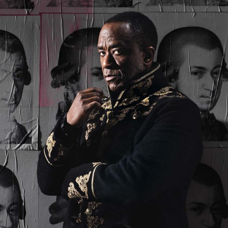 Amadeus poster. Photo of Lucian Msamati, as Salieri, standing against a wall of posters of Mozart