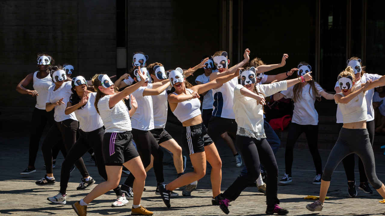 A photo of young people dancing in panda masks as part of a NT Youth workshop