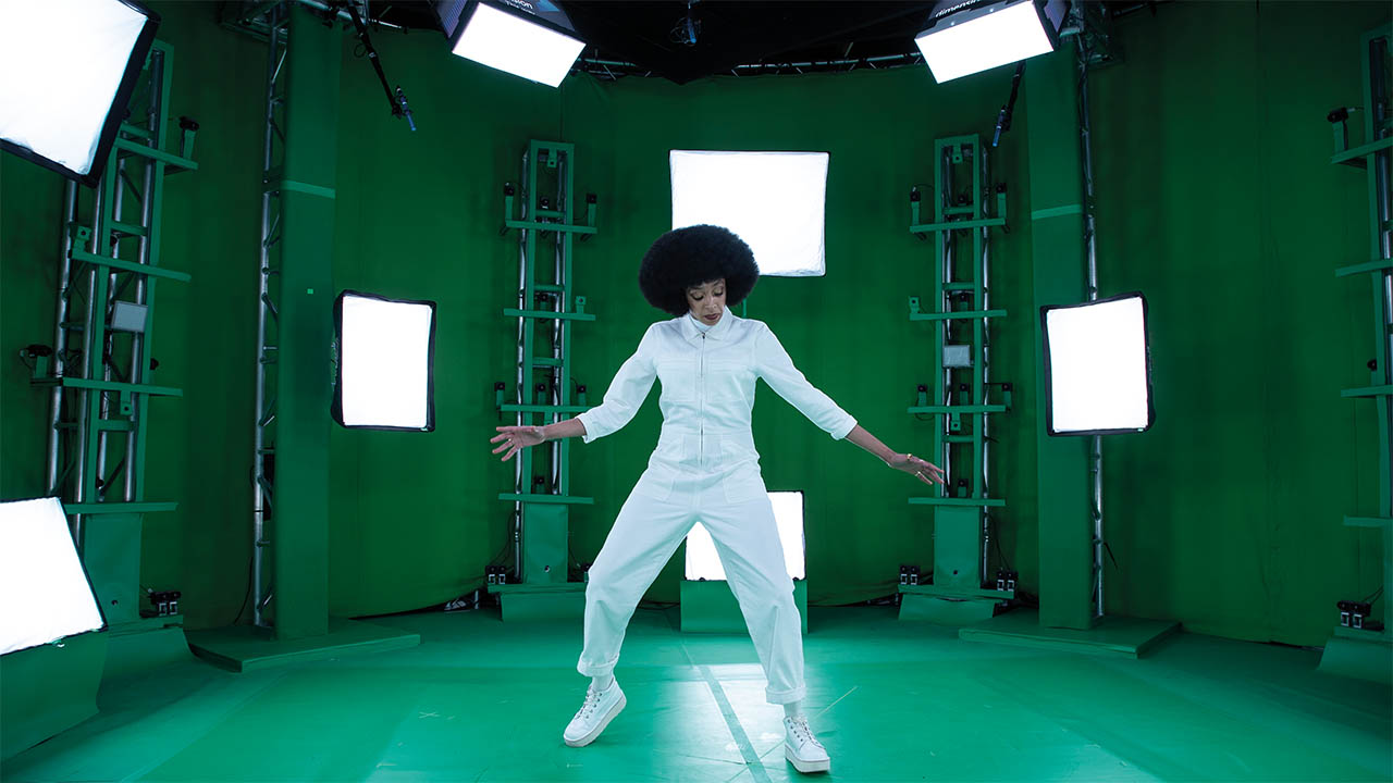All Kinds Of Limbo photo of Nubiya Brandon in a white jump-suit in a green room with cameras