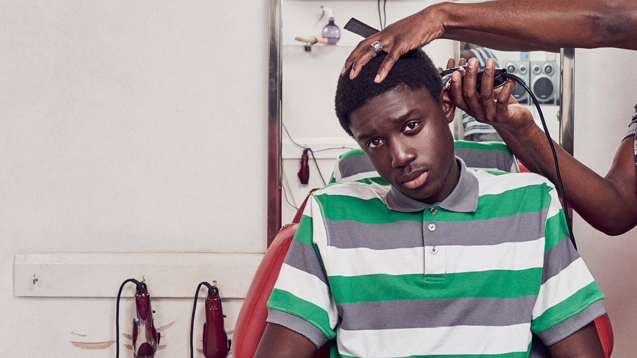 Barber Shop Chronicles - a young man having his hair clipped