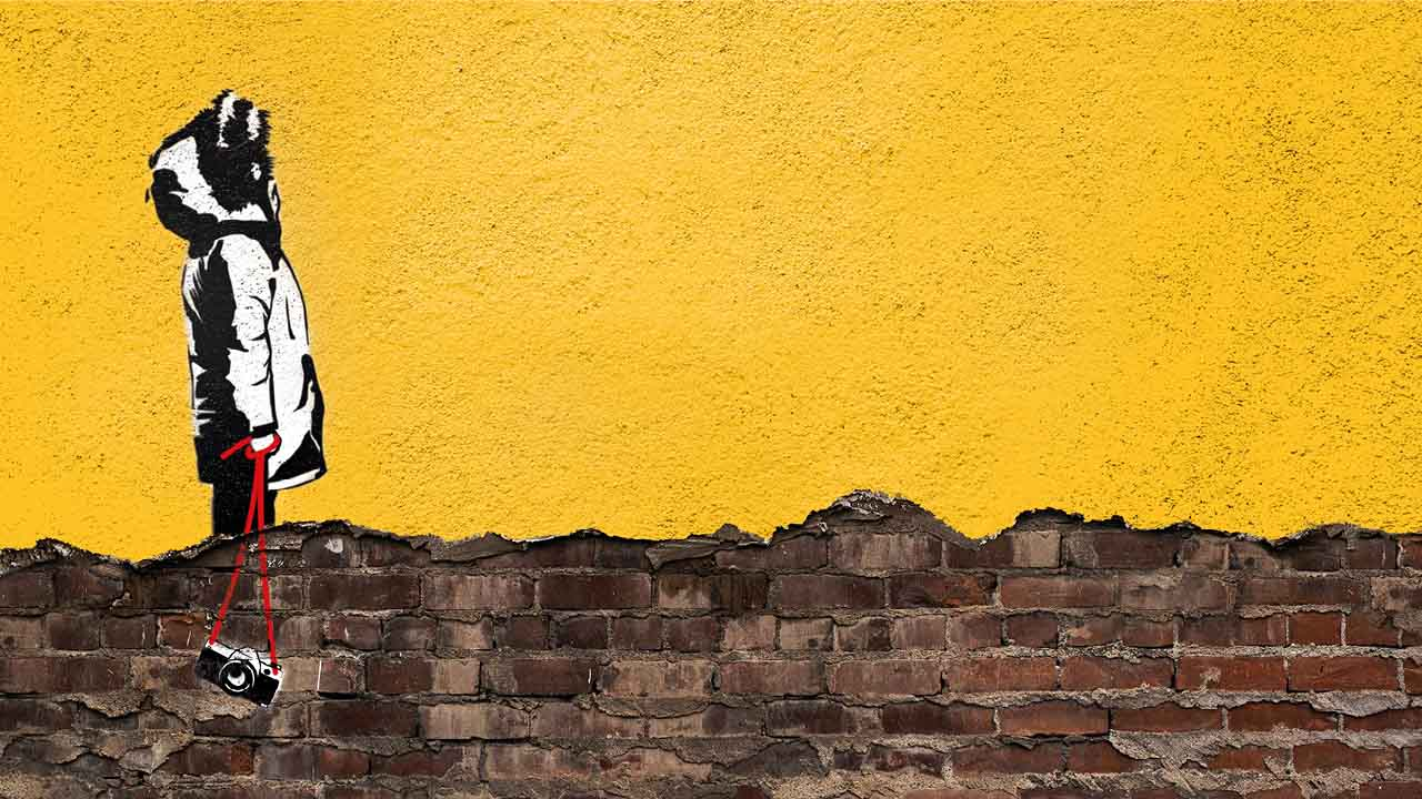 East is East graffitied image with a figure in profile, wearing a parka coat on a rendered, yellow wall.