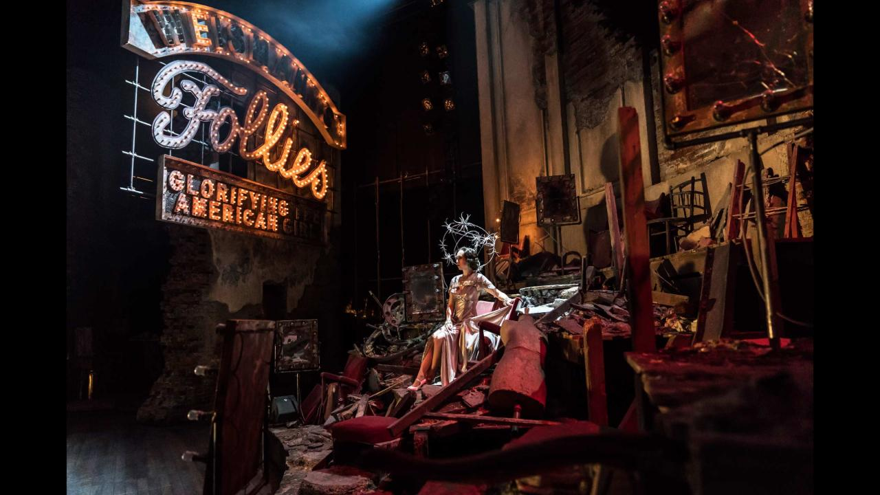 Follies set with figure seated amongst theatrical debris
