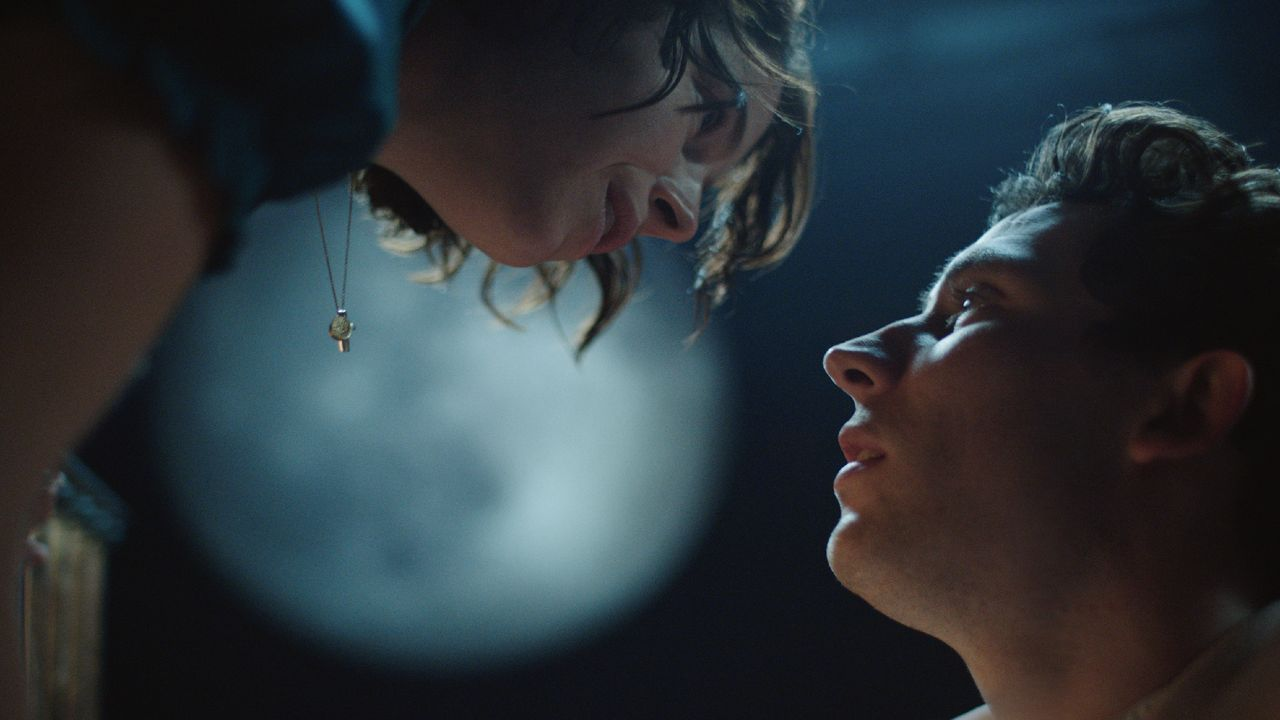 Romeo and Juliet. Photo of the two lovers (Jessie Buckley and Josh O'Connor) Romeo looking up into Juliet's downturned face, an out-of-focus moon in the background