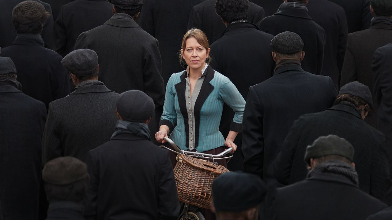 The Corn is Green with Nicola Walker. A photo of Nicola Walker pushing her bicycle towards the camera, through a crowd of black coated miners all walking away from camera