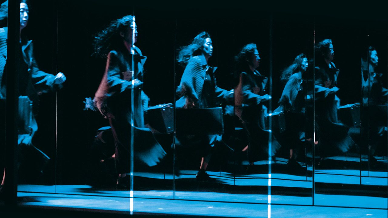 The Seven Streams of the River Ota - photo from the show, of a woman running, carrying a suitcase, reflected multiple times across the image