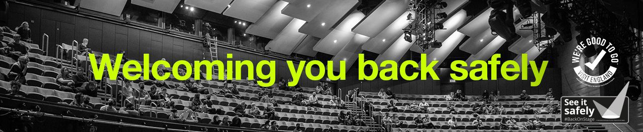 Welcoming You Back Safely, banner message overlaid on a black and white gradient photo of the Olivier Theatre with socially distanced audience, with the Visit England Good to Go and See it Safely logos