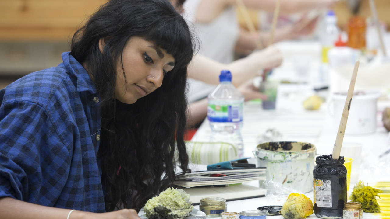An image of a young participant using different craft materials in a creative workshop
